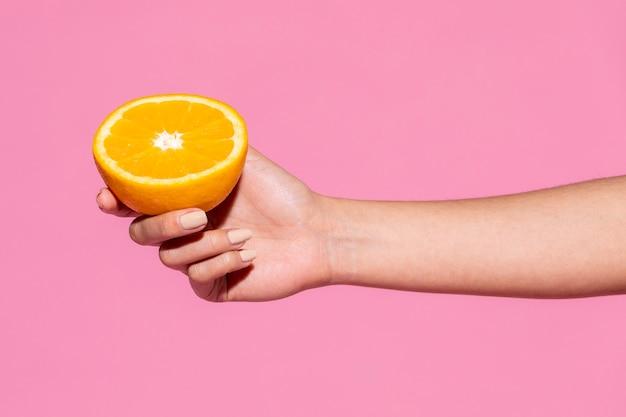 분홍색 배경에 반 오렌지를 들고 있는 여자