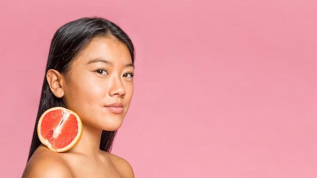 Woman holding half of grapefruit on her shoulder