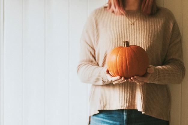 Женщина, держащая тыкву на хэллоуин в осеннем настроении фермерского дома