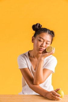 Woman holding halves of lemon with her eyes closed