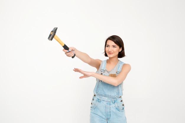 Женщина держит молоток, делает ремонтные работы