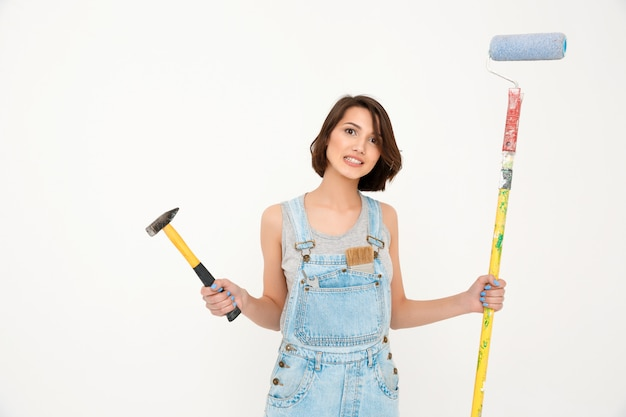 Woman holding hammer and painting brush, renovating house