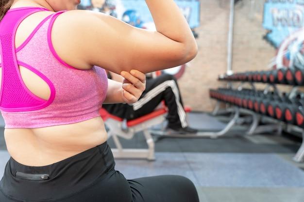 Женщина, держащая руку чрезмерно толстую руку в тренажерном зале