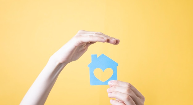 Woman holding hand over figure of wooden house on a yellow background.