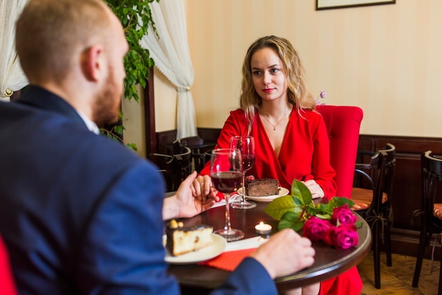 Woman holding hand of man at table