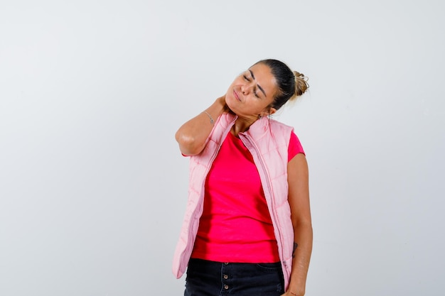 Woman holding hand on neck in t-shirt, vest and looking fatigued