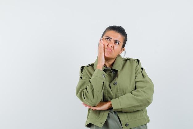 Женщина держит руку на щеке в куртке, футболке и смотрит задумчиво.