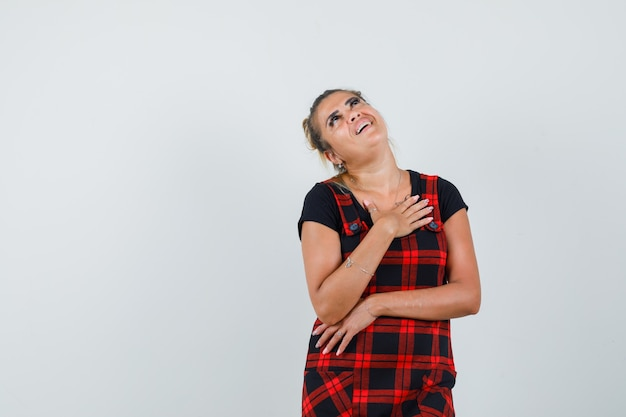 ピナフォアのドレスで胸に手をつないで、夢のように見える女性。正面図。