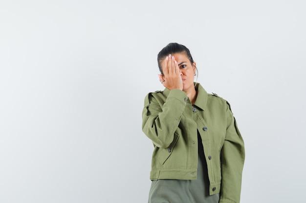 여자 재킷, t- 셔츠에 눈에 손을 잡고 잠겨있는 찾고.