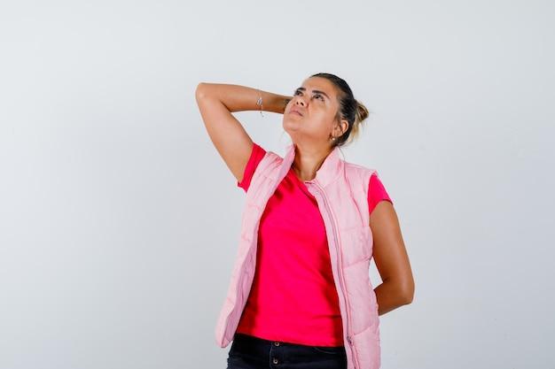 Женщина держит руку на голове в футболке, жилете и выглядит задумчиво