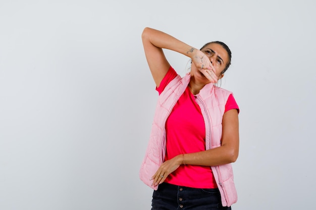 Женщина держит руку на рту в футболке, жилете и выглядит задумчиво