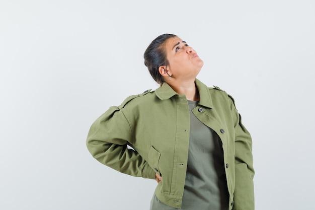 Женщина держит руку на талии в куртке, футболке и смотрит задумчиво