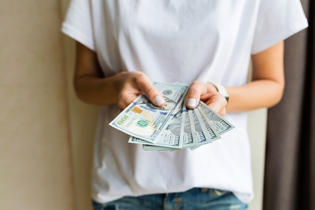 Woman holding hand one hundred dollar bills