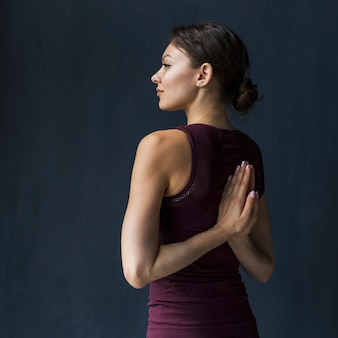 Woman holding hand in a praying pose behind her back