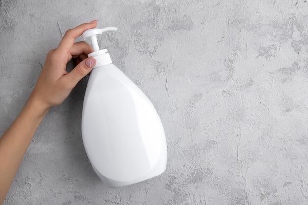 Женщина, держащая дезинфицирующее средство для рук или мыло.