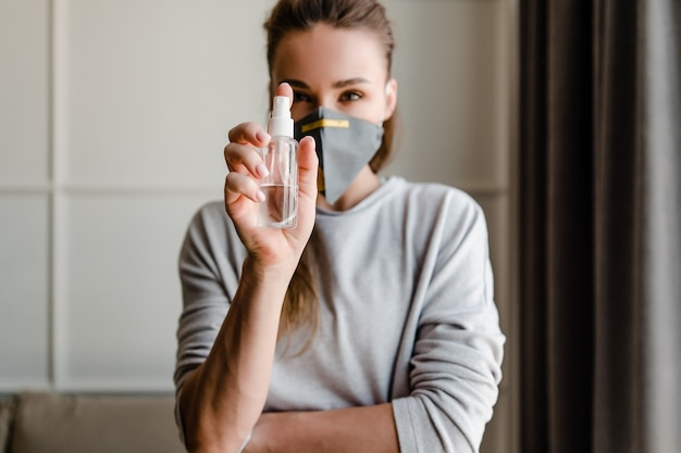 Woman holding hand sanitizer wearing protective mask at home