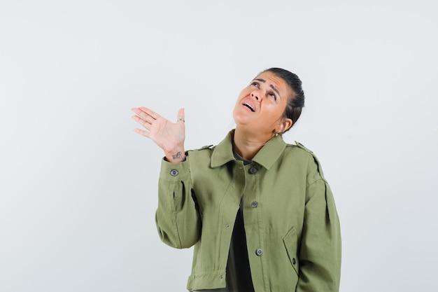 ジャケット、tシャツで方向を示すために手を握って困惑している女性。