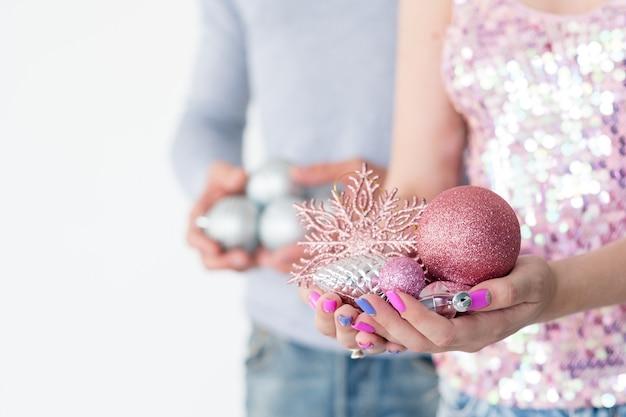 Женщина держит горсть блестящих шаров из розового золота и снежинки