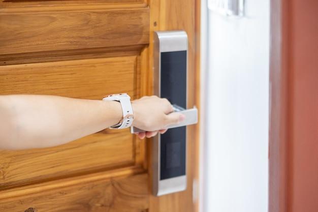 스마트 디지털 도어 잠금 핸들을 잡고여자가 문을 열거 나 닫습니다. 기술, 전기 및 라이프 스타일 개념