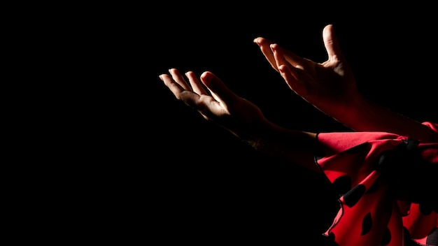 Woman holding hands on black background