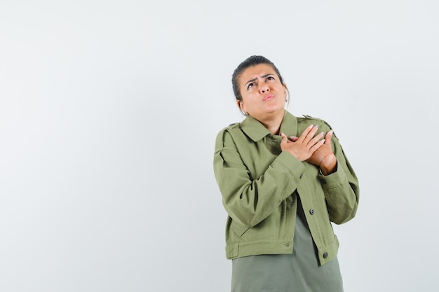 Woman holding hands on heart in jacket, t-shirt and looking anxious.