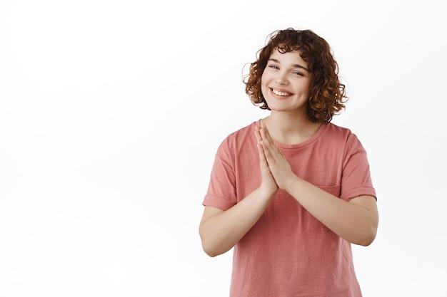祈りのナマステで手をつないでいる女性は、丁寧に手を一緒に押して、感謝し、感謝し、白のtシャツに立っています。