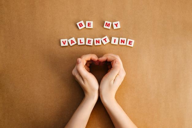 Be my valentinetextの隣にハートの形で手をつないでいる女性。