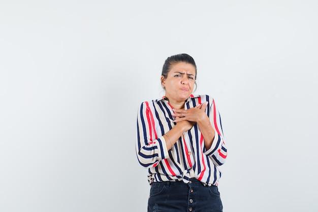 Женщина, взявшись за руки на груди в рубашке, юбке и глядя расстроенной.