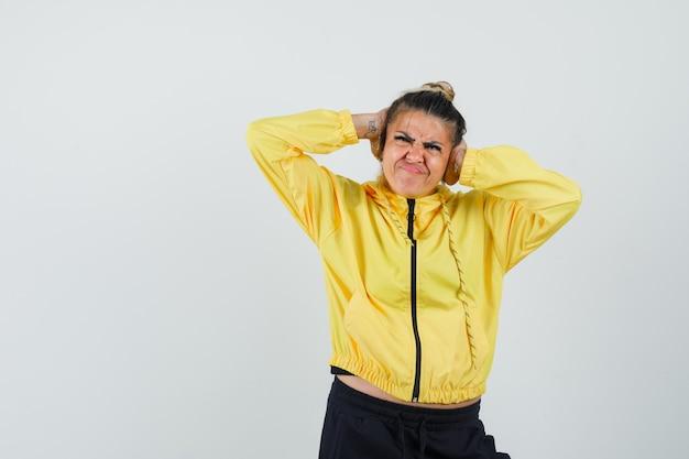Женщина держится за уши в спортивном костюме и выглядит раздраженной. передний план.