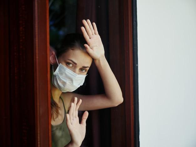 ロックダウン医療マスクを身に着けている窓に手をつないでいる女性