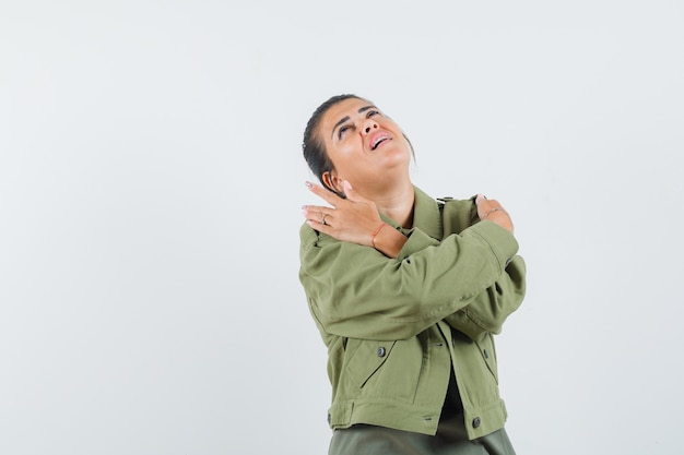 Donna che tiene le mani sulle spalle in giacca, t-shirt e sembra sognante