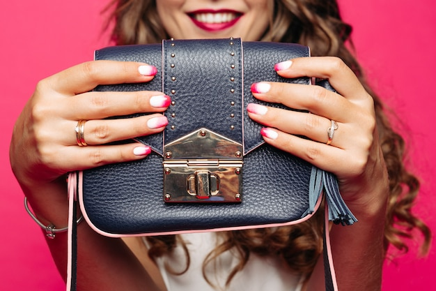Woman holding at hands and showing blue leather handbag.