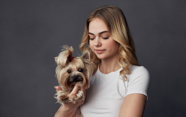 Женщина держится за руки маленькая породистая собака дружба объятие радость серый фон