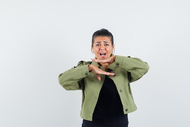 ジャケット、tシャツ、かわいく見えるあごの下で手をつないでいる女性。