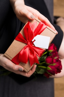 Woman holding in hands valentine's day gift and roses
