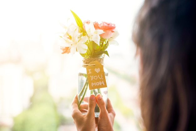 Woman holding in hands vase of flowers for mother`s day