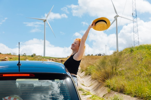 Woman holding hat in arm outstretched out of car window