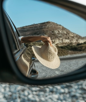 Woman holding hat out of window in car mirror view