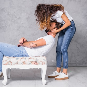Woman holding head of man on chair
