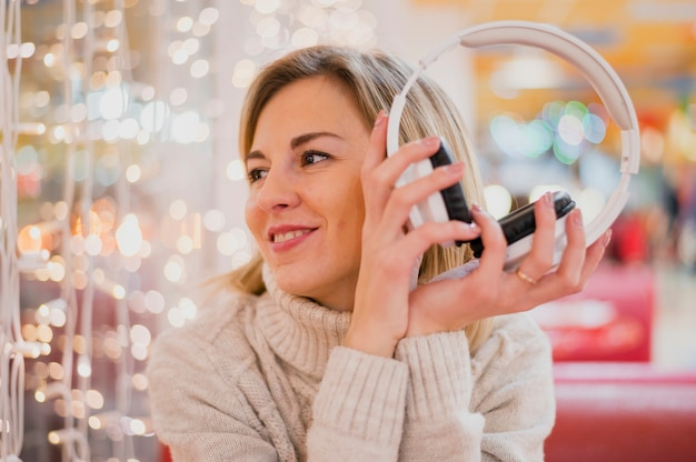 Woman holding headphones looking at christmas lights
