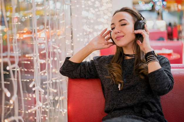 クリスマスライトの近くの頭の上のヘッドフォンを保持している女性