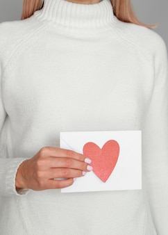 Woman holding heart envelope studio shot