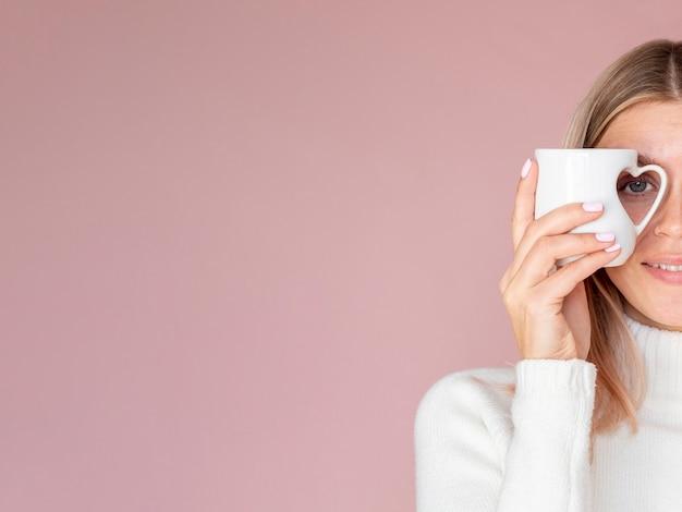 Woman holding heart mug copy space