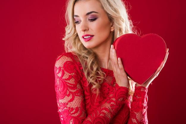 Женщина держит коробку в форме сердца рядом с ее лицом