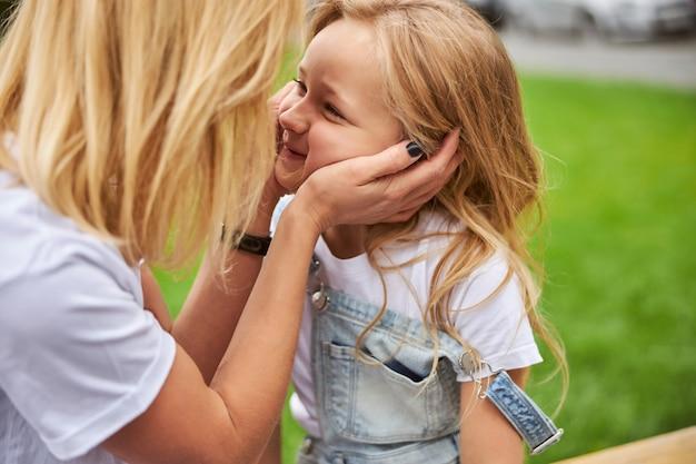 행복한 아이가 야외에서 그녀의 어머니를 찾고있는 동안 그녀의 딸 얼굴에 그녀의 팔을 들고 여자