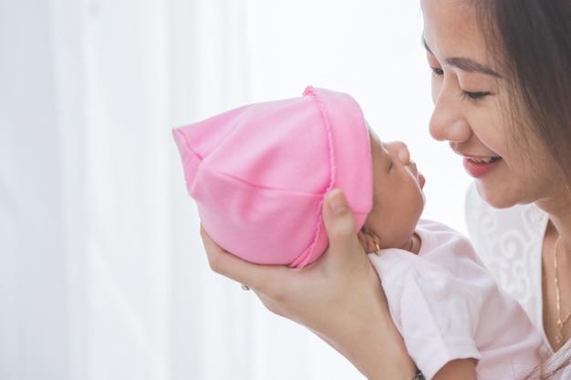 彼女の女の赤ちゃんを保持している女性をクローズアップ