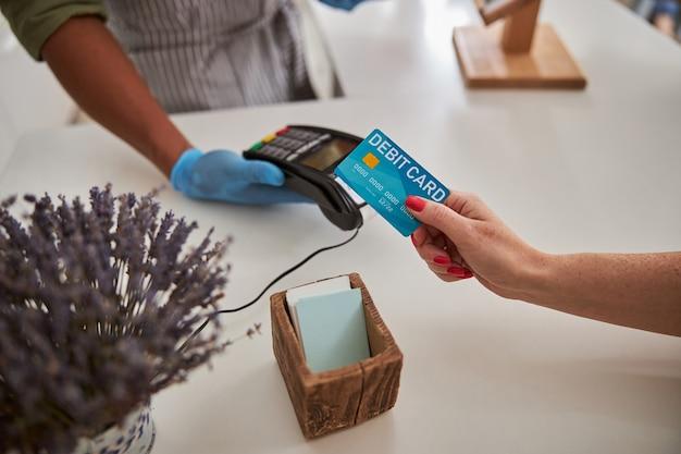그녀의 구매를 위해 돈을 이체하는 동안 꽃집 가게 터미널 위에 그녀의 파란색 신용 카드를 들고 여자