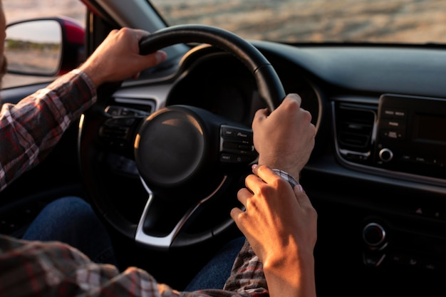 Woman holding her boyfriends hand while driving