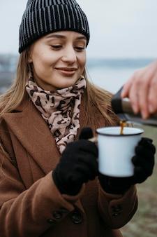 屋外で温かい飲み物を飲むために彼女のカップを保持している女性