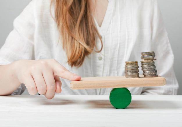 Женщина держит палец в балансе с монетами